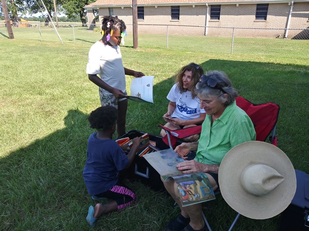 Ms. Linda and Mrs. Everett reading books to kids