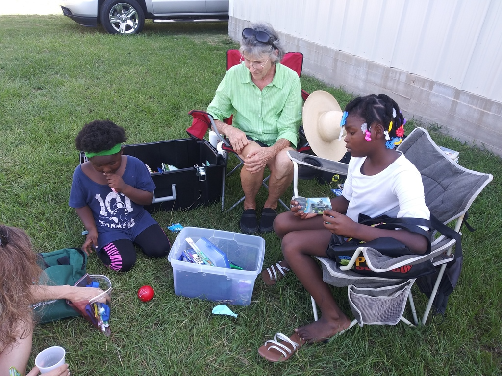 Ms. Linda sitting and talking with kids