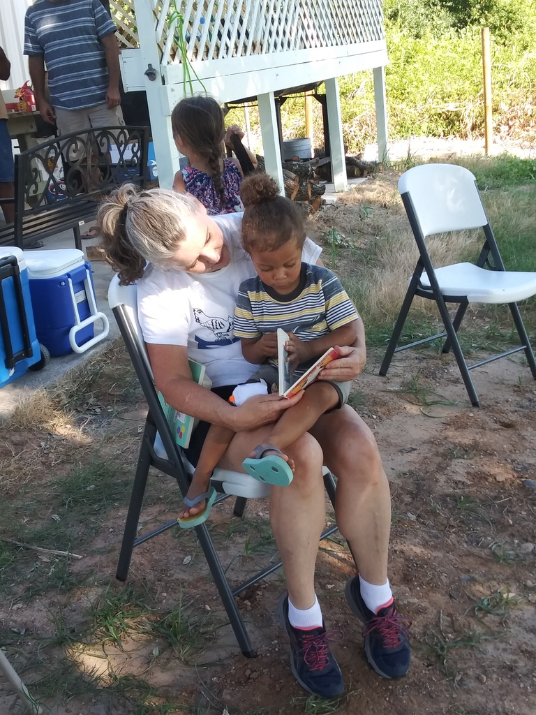 Ms. Kirk reading to a child.