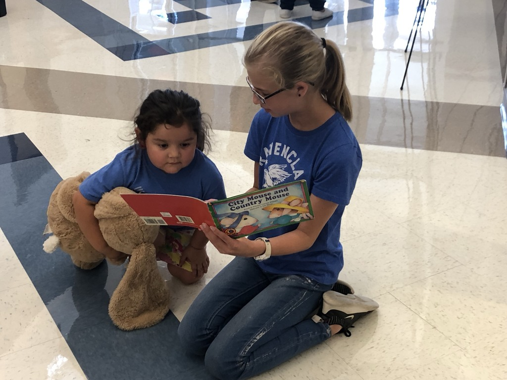 one student reading a book to an other students