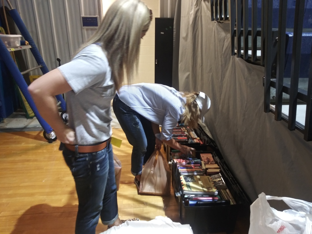 Parent picking books with Volleyball girl