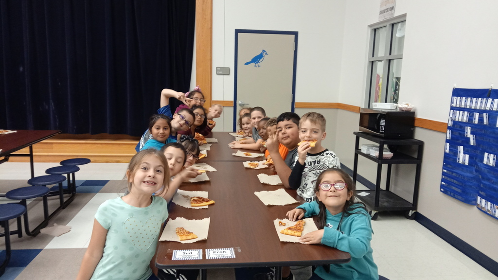 Kids eating pizza at a pizza part for perfect attendance the first six-weeks of school. 5